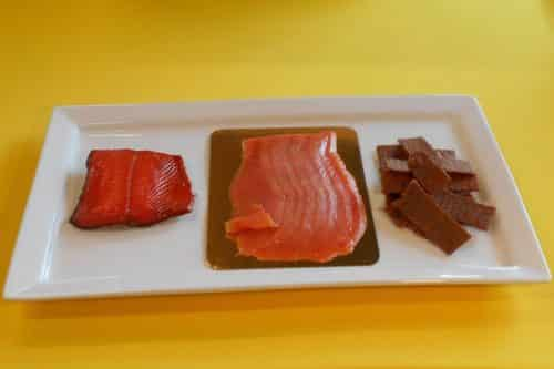 Entertainer: Hot Smoked Wild Alaskan Sockeye Salmon, one 5 oz sliced king lox on gold display board, smoked salmon jerky - Plated