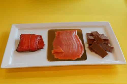 Entertainer: Hot Smoked Wild Alaskan Sockeye Salmon, one 5 oz sliced king lox on gold display board, smoked salmon jerky - Plated
