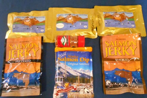 Trappers Cache Gift Pack; 4 oz Pacific Salmon Maple Flavor, 4 oz Pacific Salmon Smoked, 4 oz Pacific Salmon Garlic Pepper Flavor in 3 individual pouches. A bottle of Alaska Bits, the Bacon Bit Alternative, a 6 oz pouch of Salmon Dip, and one 3 oz pack each of Smoked Salmon Jerky and Peppered Salmon Jerky